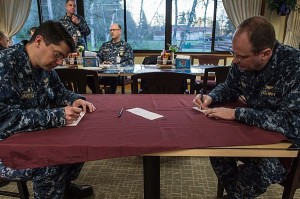 Rear Adm. Jeffrey Ruth, commander of Navy Region Northwest, and Capt. Mike Baretela, commanding officer of Strategic Weapons Facility Pacific, fill out donation slips for the Navy-Marine Corps Relief society, which provides interest-free loans and grants, budget and financial counseling and other service for Sailors and Marines. (U.S. Navy photo by Mass Communication Specialist 3rd Class Seth Coulter/Released)