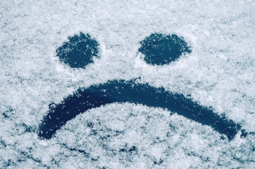 Sad smiley emoticon face drawn on snow covered glass